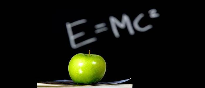 Une pomme verte et une formule inscrite sur un tableau noir, en guise de soutien à l'enseignement