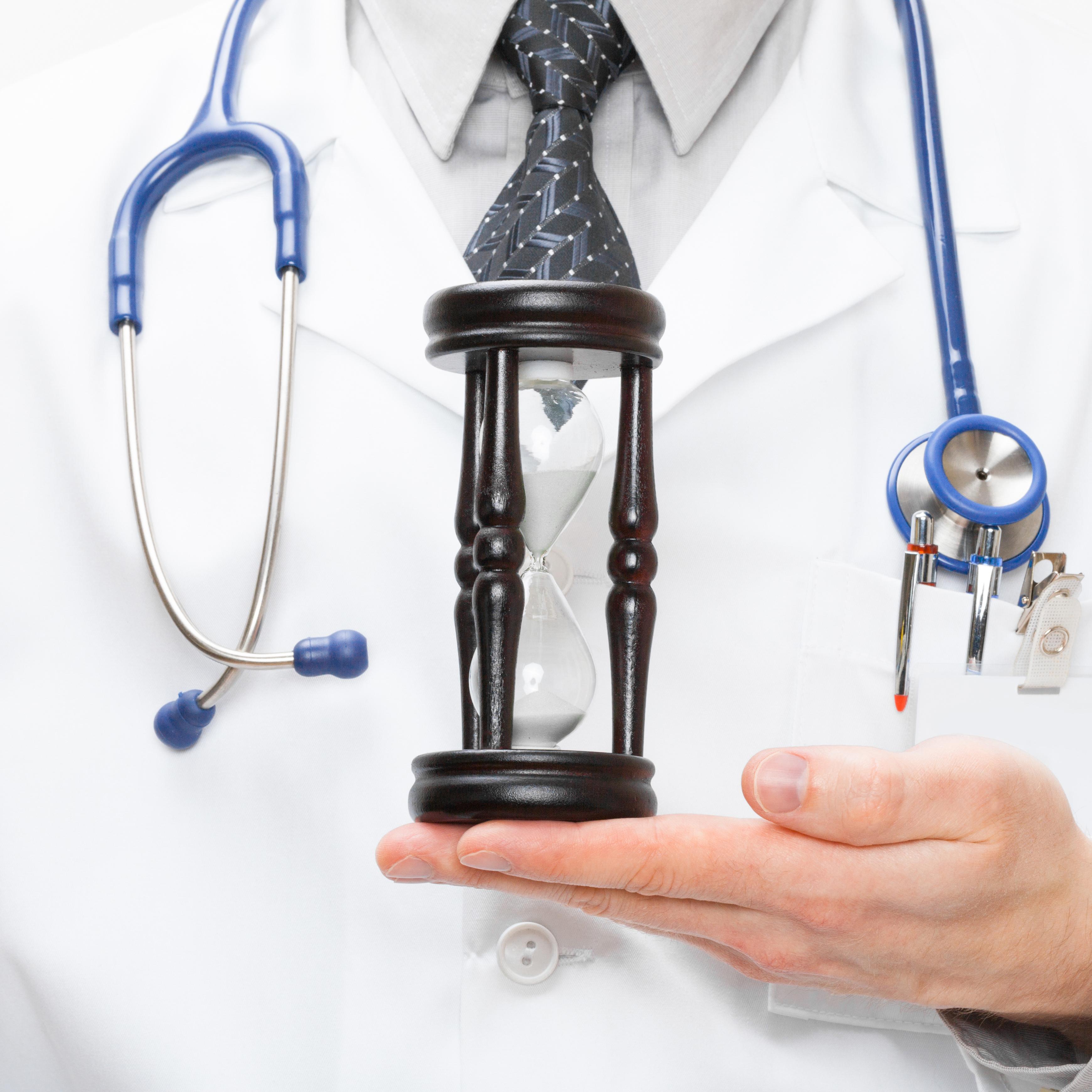 Médecin présentant un sablier pour démontrer le temps nécessaire è implanter un changement