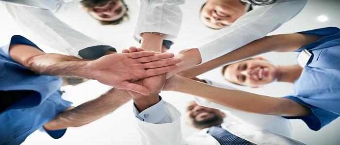 Gens qui forment un cercle et qui mettent leurs mains une par-dessus l'autre.