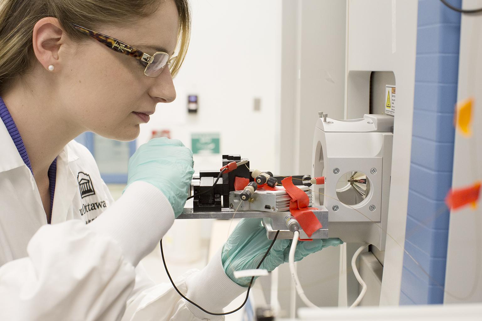 Graduate Student working on a Mass Spec instrument