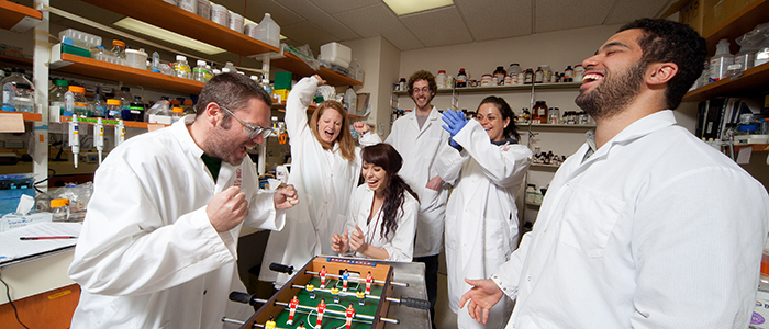 Students laughing in lab over a foozball table