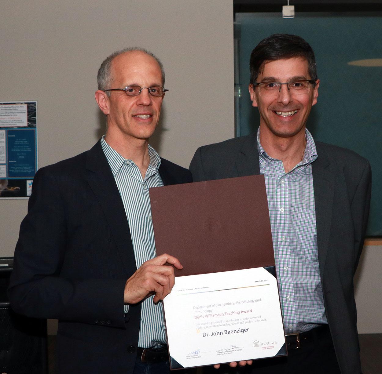 Dr. John Baenziger accepting a award from Dr. Daniel Figeys