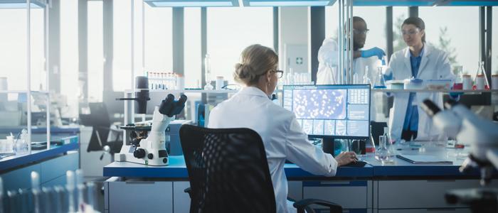 Microbiologiste qui en regarde d'ADN sur un ordinateur dans un laboratoire