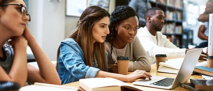 Etudiantes qui travaillent ensemble dans une bibliothèque.