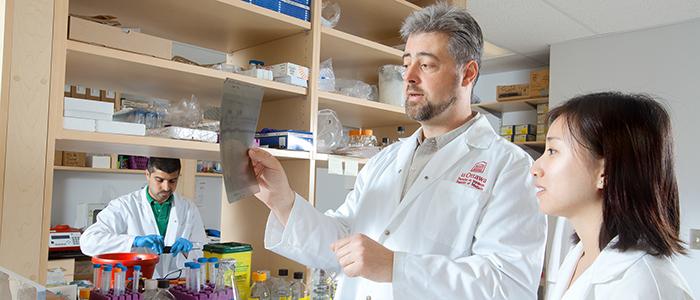 Membre du corps professoral en compagnie d'un étudiant dans le laboratoire de science