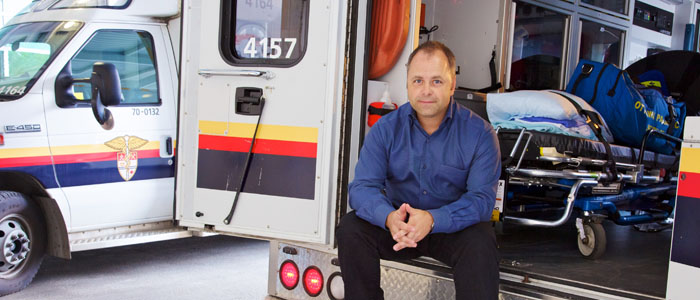 Male Emergency Physician sitting at the back of Ambulance with doors open