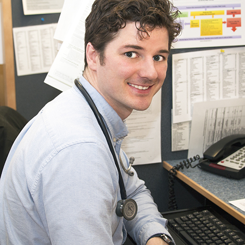A family medicine resident sits at his desk between patient visits.