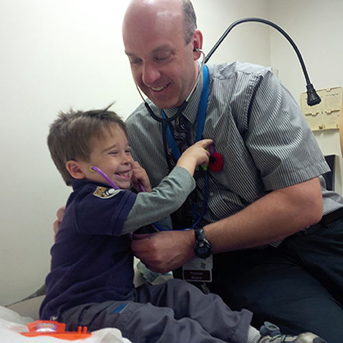 Dr. Eric Wooltorton, a DFM faculty member, with a young patient at the Civic teaching unit.