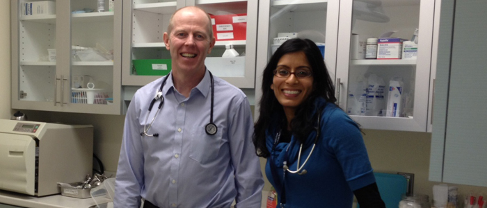 Dr. Jeff Hovey and Dr. Shirin Lal, DFM preceptors in a Community Teaching Site, smile in their medical office.