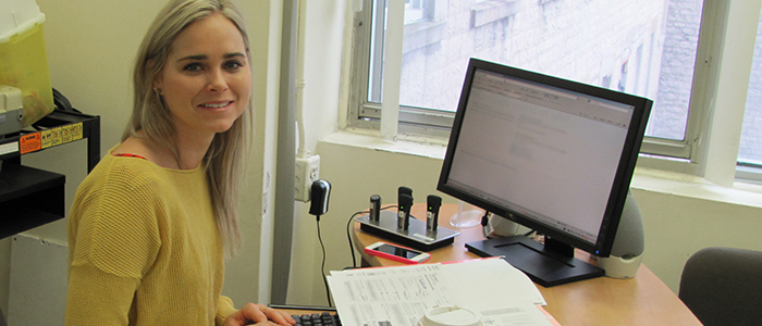 Andrea Rawley, the Community Unit Coordinator for the DFM postgraduate program, smiles at her desk.