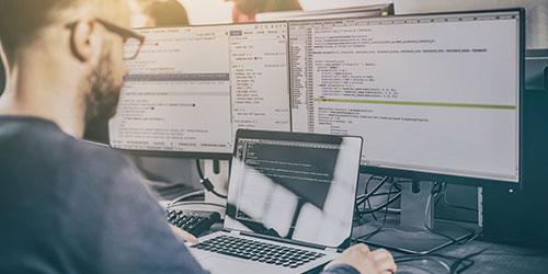 Support technique masculin travaillant sur un ordinateur portable et 2 écrans.