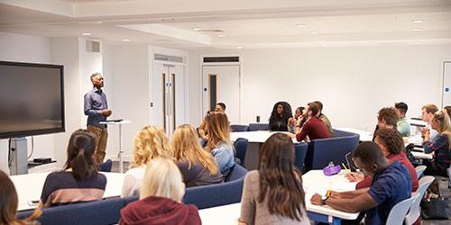 Étudiants universitaires dans une salle de classe avec un conférencier masculin.