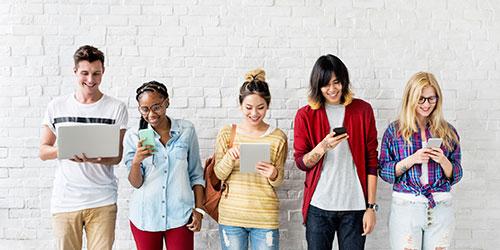 Cinq d'étudiants appuyés contre un mur utilisant divers appareils mobiles.