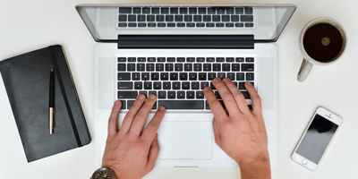 Hands of a man typing on a computer on a table with a notebook, a coffee and a cellphone