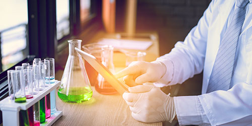 Scientist man with glasses working tablet research and conducts experiments by synthesising compounds in laboratory and the test tube