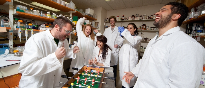 Students in lab coats playing foosball