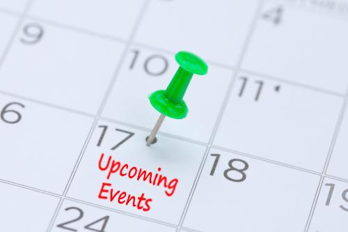 Gros plan d'un calendrier avec une punaise verte sur une date. Close up of a calendar with a green thumbtack on a date.