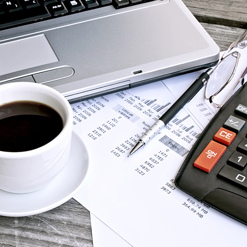 Essential payroll tools: a computer, a pen, a calculator, a paystub and a cup of coffee
