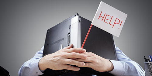 "A man, with a laptop over his head, holds a ""help!"" sign."