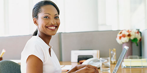 A smiling woman typing on a laptop.