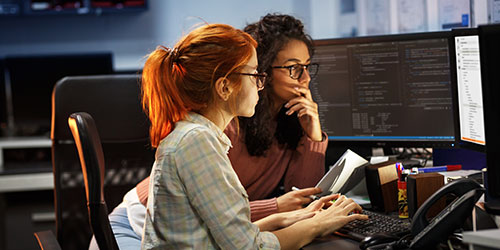 Two female programmers reviewing code on a monitor.