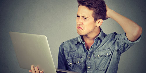 A confused man holding a laptop in his hand.