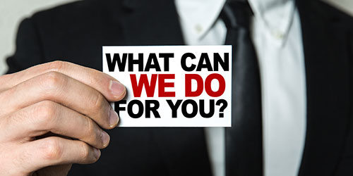 """What can we do for you?"" sign held by a male hand."