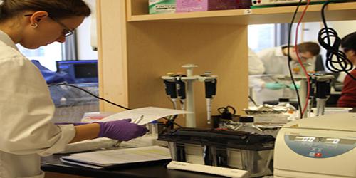 Une étudiante vêtue d'un sarreau lisant un protocole de laboratoire