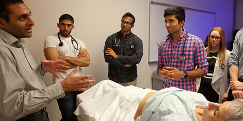 Doctor teaching a group of MD students in a clinical setting