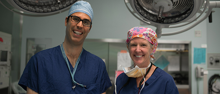 Doctors in scrubs, smiling at the camera in a surgical theatre