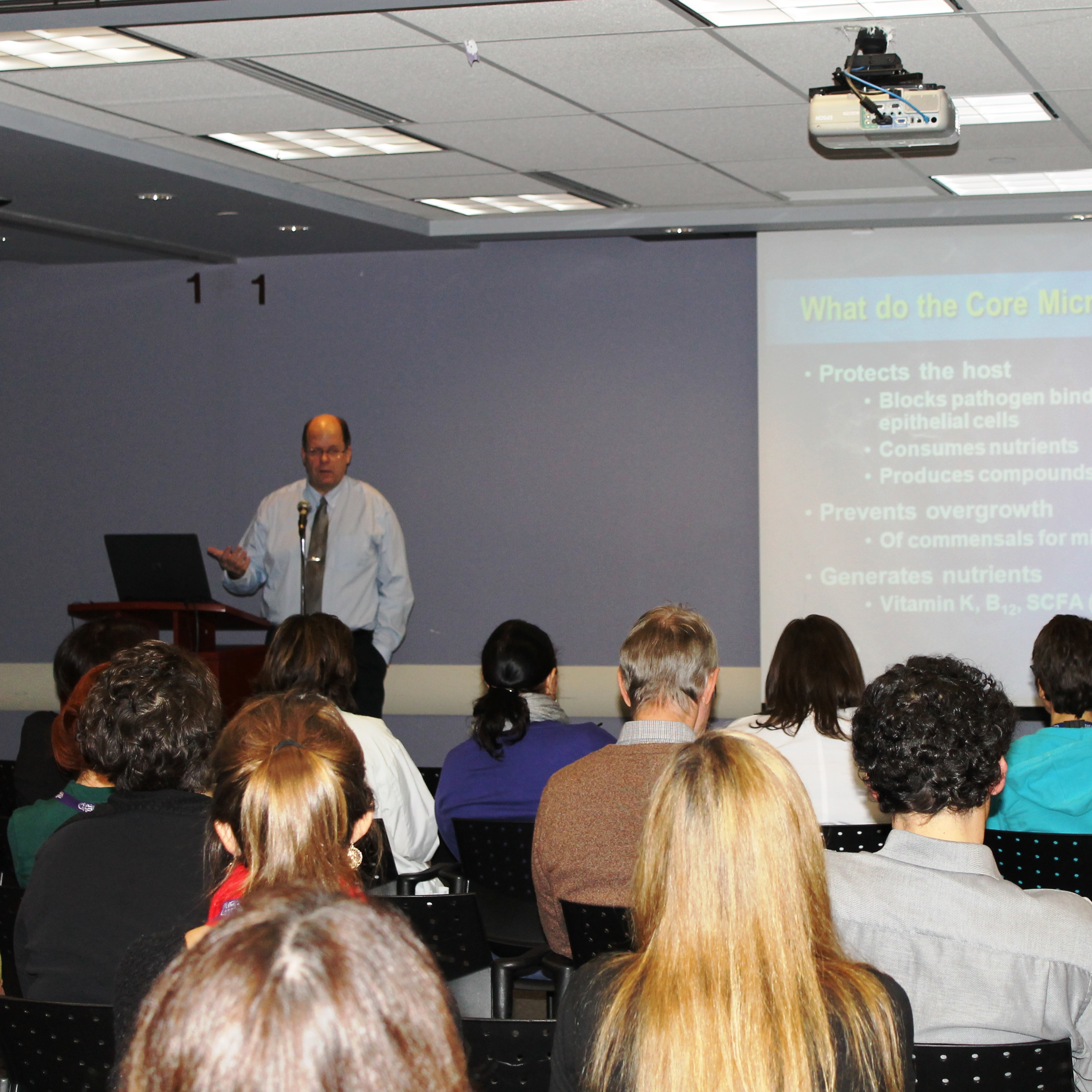 A physician presenting in front of a crowd