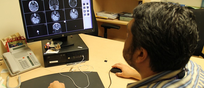 A physician examining photos of the brain
