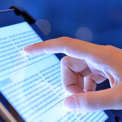Main pointant vers un écran de tablette