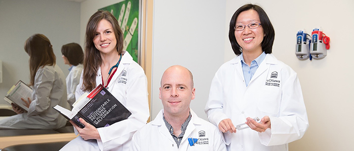 Two female doctors and one male doctor pose in their uOttawa Faculty of Medicine white coats
