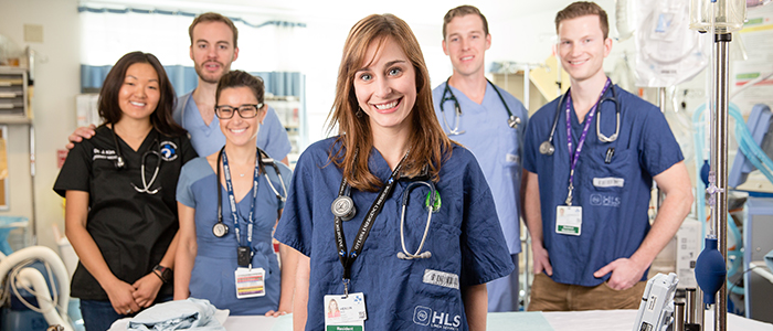 Six Emergency Medicine residents pose in their scrubs