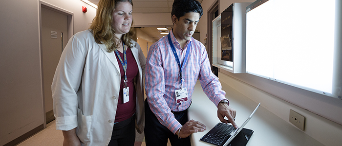 Physician provides face to face feedback to a resident, using an iPad.