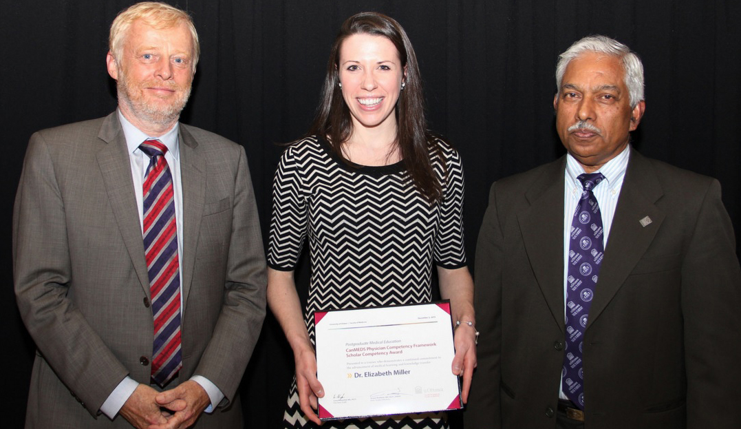 Student poses while holding a certificate accompanied by two faculty members