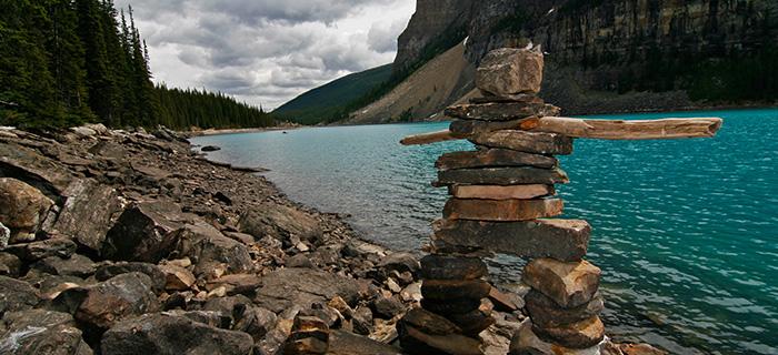 Inukshuk au bord d'un lac dans les Rocheuses canadiennes