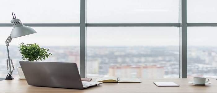 Workplace with notebook laptop. Comfortable work table in office. Windows and city view.