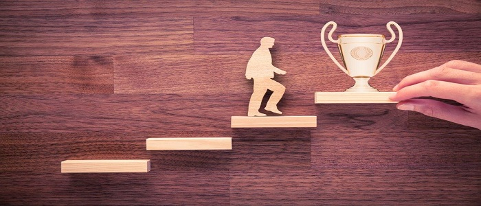 Homme montant les escaliers pour atteindre un trophée.