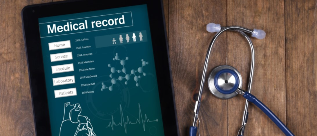 Tablet on wood table with stethoscope