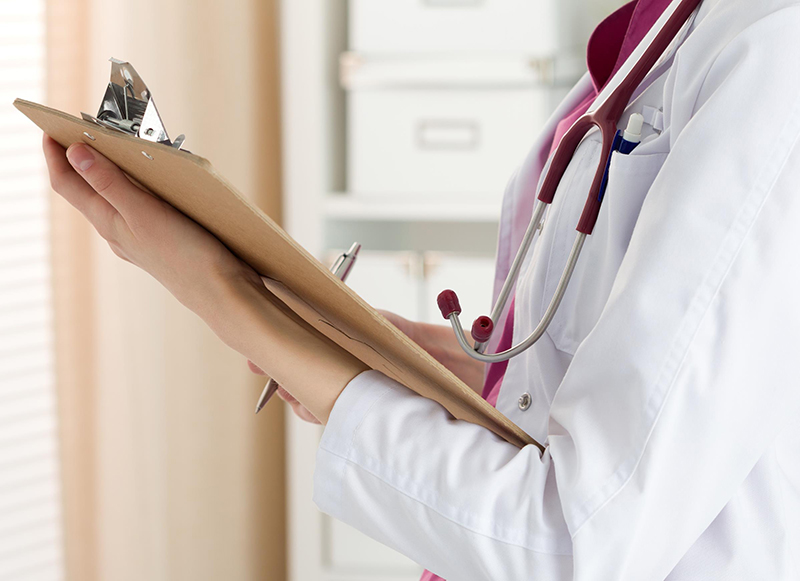 Doctor holding the patient's information note in her hand
