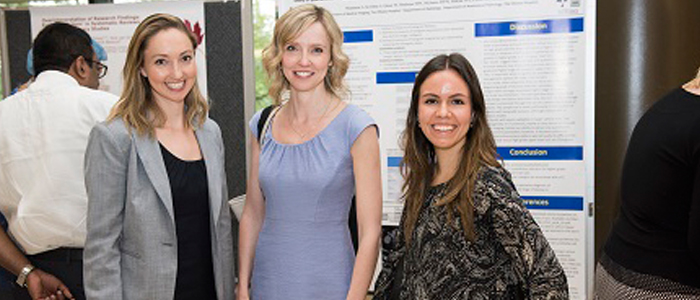 Three research in front of a poster