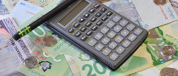 Les outils de travail essentiel pour la paie: une calculatrice, un crayon, et la monnaie
