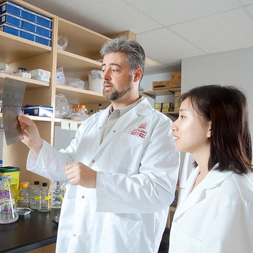 Dr Andrew Makrigiannis qui examine un rapport avec son personnel de laboratoire
