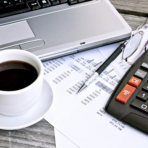 Les outils de travail essentiel pour la paie : un ordinateur, un stylo, une  calculatrice, un talon de paie et une tasse de café