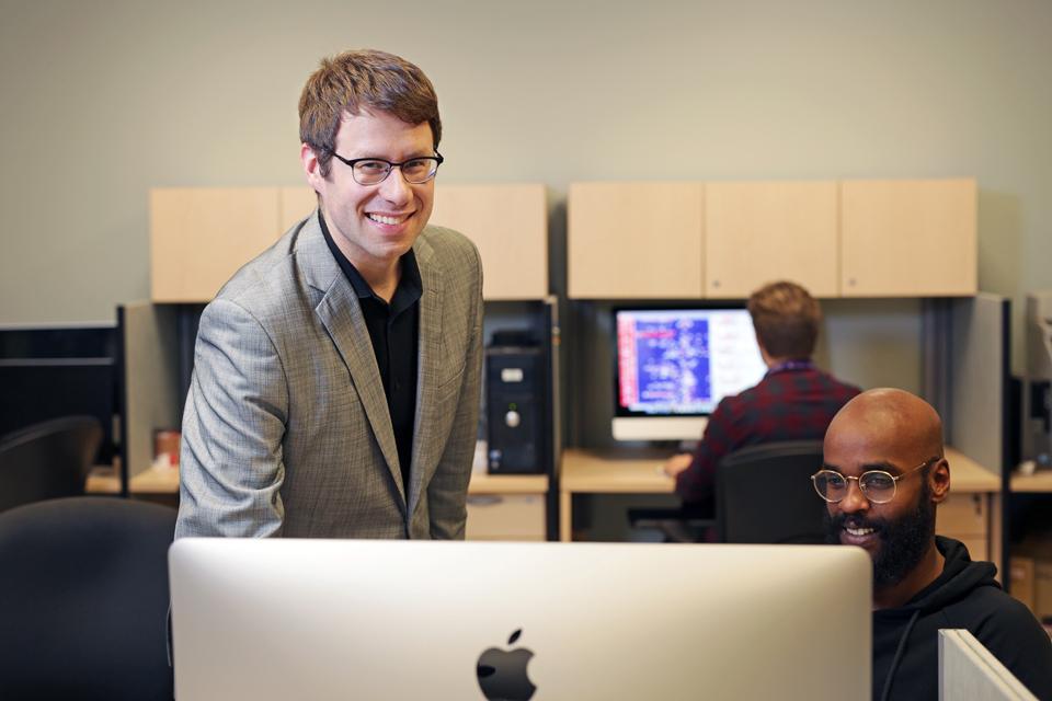 Le professeur Mathieu Lavallée-Adam debout dans un laboratoire informatique entouré d'ordinateurs.
