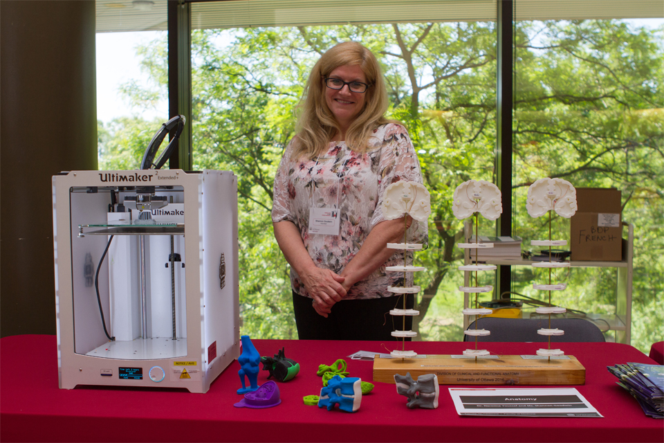 Shannon Goodwin standing behing a 3D printer and anatomical models on display.