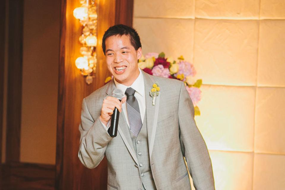 Michael Ip en costume formel et tenant un microphone