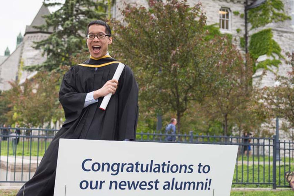 Michael Ip dans une robe de graduation et tenant un diplôme à la main
